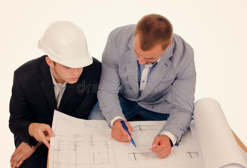 Αρσενικοί μηχανικοί που συζητούν το σχέδιο από το σχεδιάγραμμα στοκ φωτογραφίες