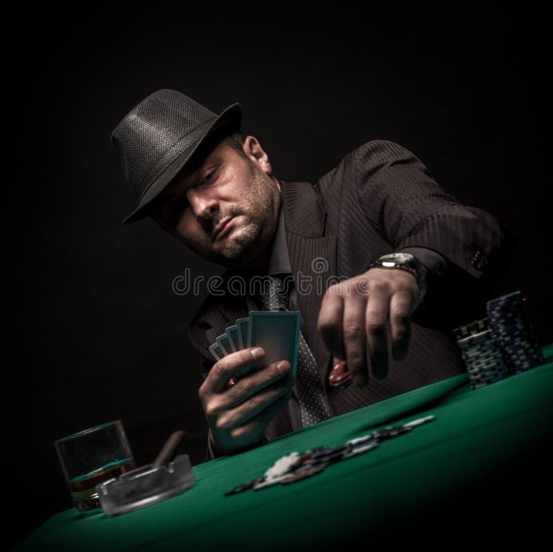 Αρσενικοί πόκερ και καπνοί παιχνιδιού παικτών ένα πούρο στοκ εικόνα με δικαίωμα ελεύθερης χρήσης