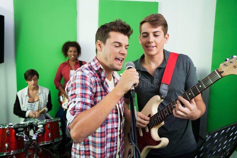 Αρσενικοί τραγουδιστές που αποδίδουν μαζί με τη ζώνη στοκ εικόνες