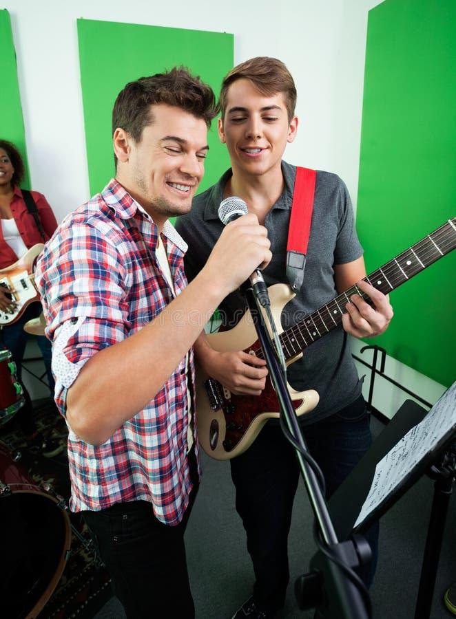 Αρσενικοί τραγουδιστές που αποδίδουν στο στούντιο καταγραφής στοκ εικόνες