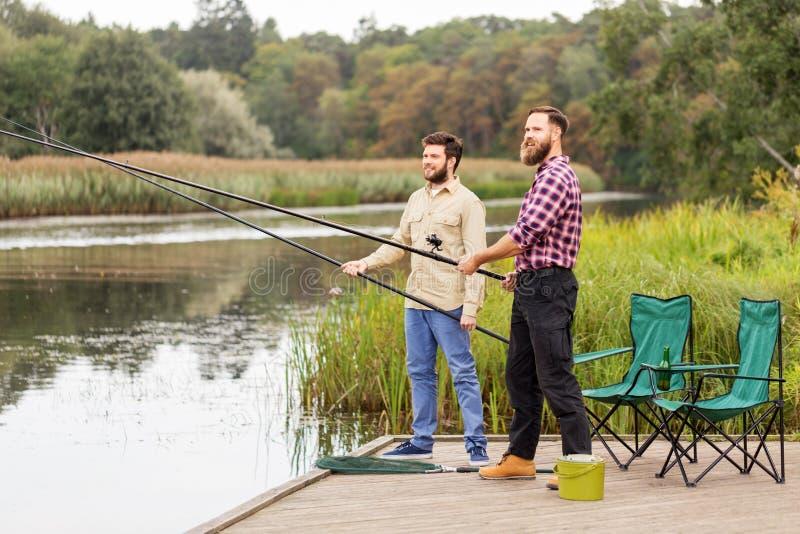 Αρσενικοί φίλοι με την αλιεία των ράβδων στην αποβάθρα λιμνών στοκ εικόνα