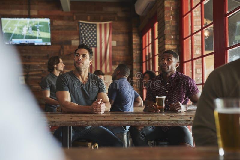 Αρσενικοί φίλοι που πίνουν την μπύρα και που προσέχουν το παιχνίδι στην οθόνη στον αθλητικό φραγμό στοκ εικόνα με δικαίωμα ελεύθερης χρήσης