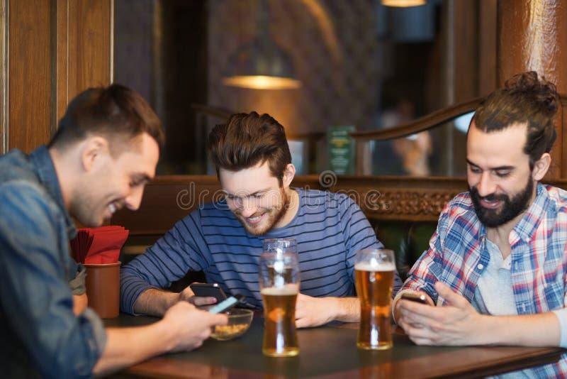 Αρσενικοί φίλοι με τα smartphones που πίνουν την μπύρα στο φραγμό στοκ φωτογραφία