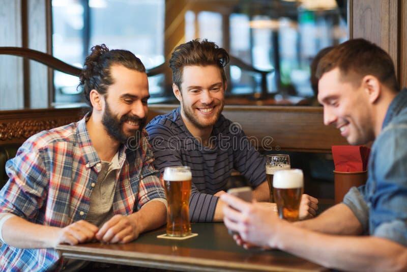 Αρσενικοί φίλοι με την μπύρα κατανάλωσης smartphone στο φραγμό στοκ εικόνες