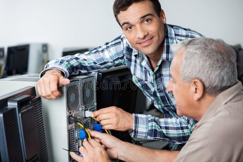 Αρσενικός δάσκαλος που βοηθά το ανώτερο άτομο στον καθορισμό του υπολογιστή στοκ εικόνα