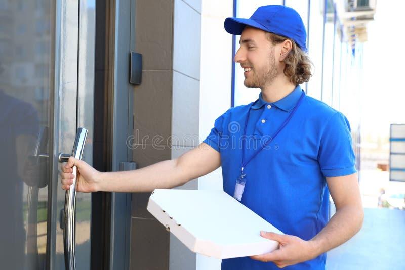 Αρσενικός αγγελιαφόρος με την πίτσα στην είσοδο i στοκ φωτογραφίες με δικαίωμα ελεύθερης χρήσης