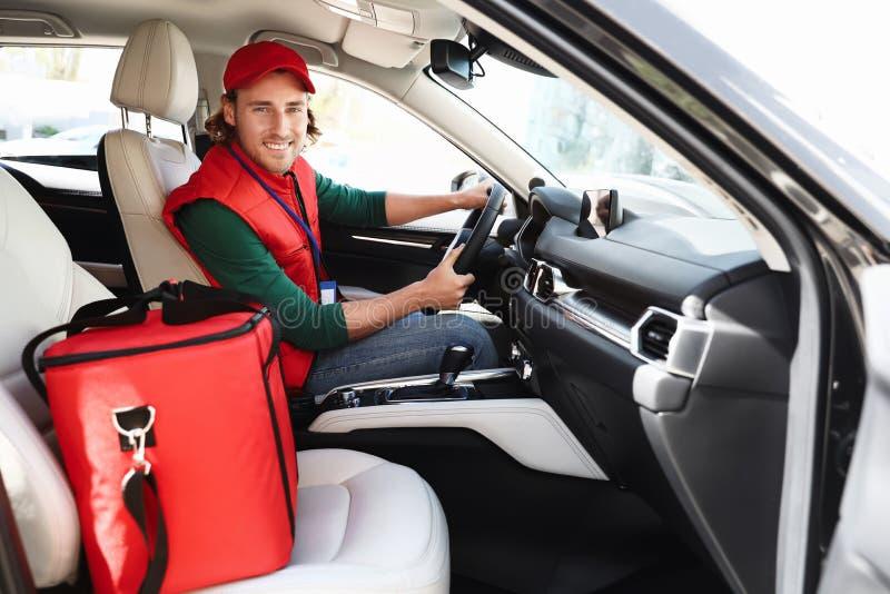 Αρσενικός αγγελιαφόρος με τη θερμο τσάντα στο αυτοκίνητο i στοκ φωτογραφίες