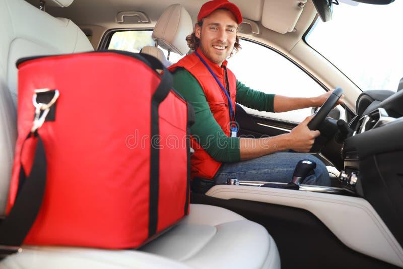 Αρσενικός αγγελιαφόρος με τη θερμο τσάντα στο αυτοκίνητο i στοκ φωτογραφία