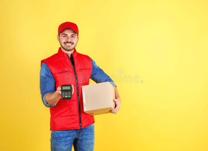 Αρσενικός αγγελιαφόρος με το δέμα και τερματικό πληρωμής στο υπόβαθρο χρώματος στοκ εικόνες