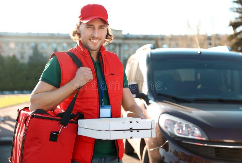 Αρσενικός αγγελιαφόρος που παραδίδει τα τρόφιμα στην πόλη στοκ εικόνα