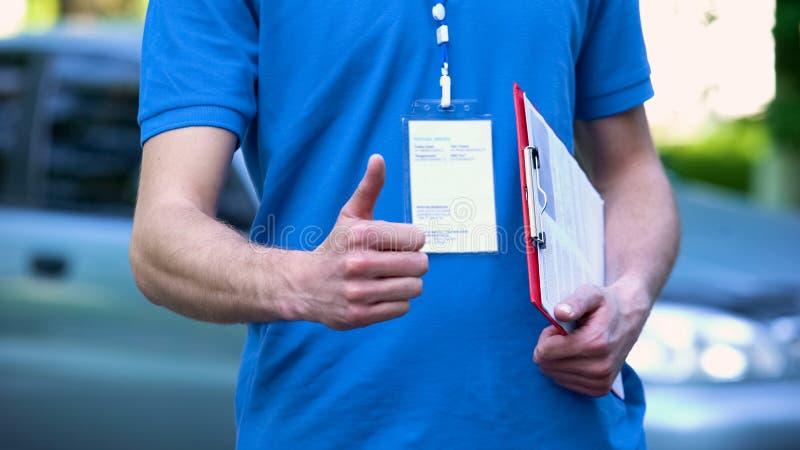 Αρσενικός αγγελιαφόρος που παρουσιάζει αντίχειρες, ποιοτική υπηρεσία αποστολών, σαφής παράδοση στοκ εικόνα