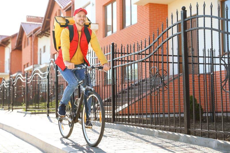 Αρσενικός αγγελιαφόρος στο ποδήλατο που παραδίδει τα τρόφιμα μέσα στοκ φωτογραφία με δικαίωμα ελεύθερης χρήσης