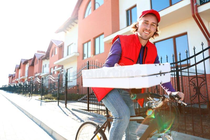 Αρσενικός αγγελιαφόρος στο ποδήλατο που παραδίδει τα τρόφιμα μέσα στοκ εικόνες