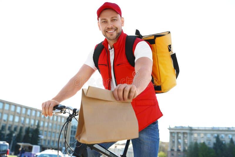 Αρσενικός αγγελιαφόρος στο ποδήλατο που παραδίδει τα τρόφιμα στοκ φωτογραφία