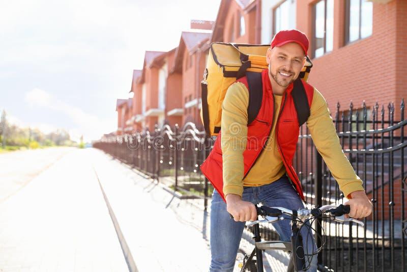 Αρσενικός αγγελιαφόρος στο ποδήλατο που παραδίδει τα τρόφιμα στοκ φωτογραφίες με δικαίωμα ελεύθερης χρήσης