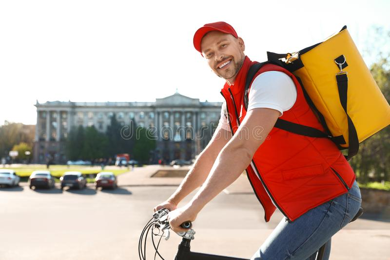 Αρσενικός αγγελιαφόρος στο ποδήλατο που παραδίδει τα τρόφιμα στοκ εικόνες