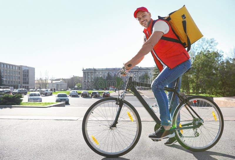 Αρσενικός αγγελιαφόρος στο ποδήλατο που παραδίδει τα τρόφιμα στοκ φωτογραφία με δικαίωμα ελεύθερης χρήσης