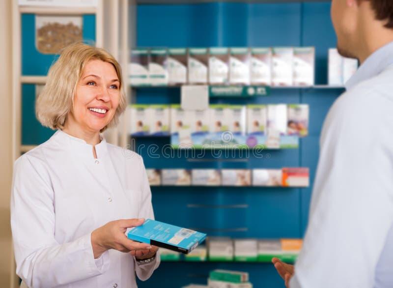 Αρσενικός αγοραστής με τον ώριμο φαρμακοποιό γυναικών στοκ φωτογραφία
