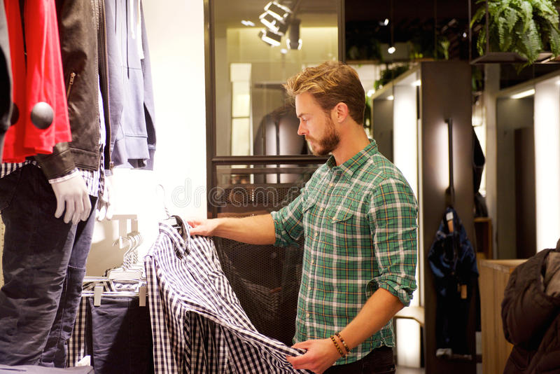 Αρσενικός αγοραστής που εξετάζει τα ενδύματα στο κατάστημα στοκ φωτογραφίες
