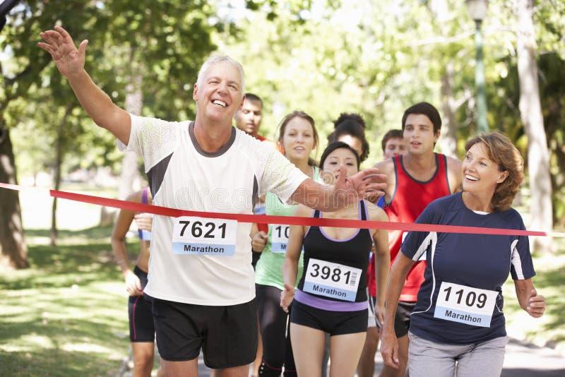 Αρσενικός αγώνας μαραθωνίου αθλητών κερδίζοντας στοκ φωτογραφία