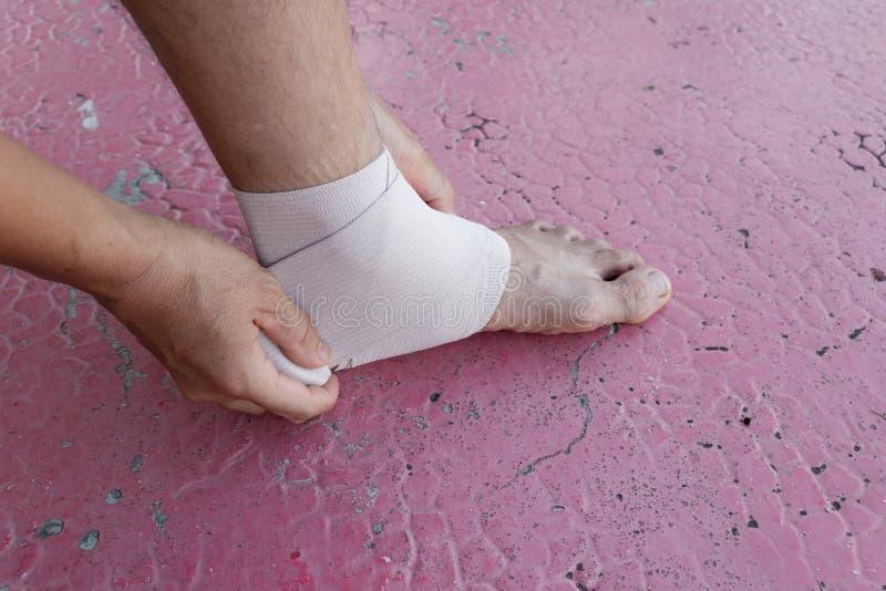 Αρσενικός αθλητής που εφαρμόζει το ύφασμα τεντωμάτων υφάσματος τεντωμάτων που τυλίγεται γύρω από τα πόδια σας στοκ εικόνες με δικαίωμα ελεύθερης χρήσης