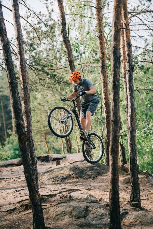 αρσενικός ακραίος ποδηλάτης στην προστατευτική εξισορρόπηση κρανών στην πίσω ρόδα του ποδηλάτου βουνών στοκ φωτογραφίες με δικαίωμα ελεύθερης χρήσης