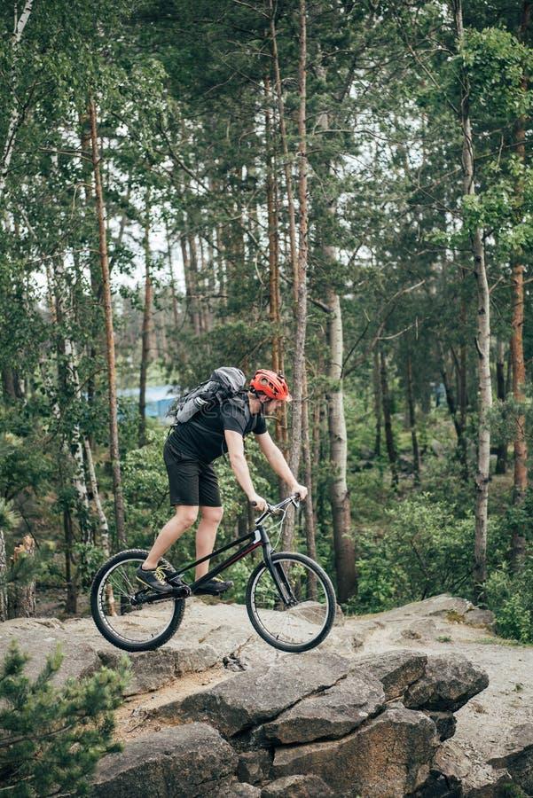 αρσενικός ακραίος ποδηλάτης στο προστατευτικό κράνος που οδηγά στο ποδήλατο βουνών στοκ φωτογραφία