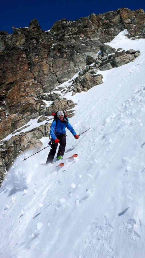 Αρσενικός ακραίος σκιέρ που κάνει σκι κάτω από ένα πολύ απότομο couloir το βαθύ χειμώνα στις ελβετικές Άλπεις κοντά σε Klosters στοκ εικόνες