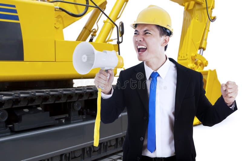 Αρσενικός ανάδοχος με megaphone και τον εκσκαφέα στοκ φωτογραφία με δικαίωμα ελεύθερης χρήσης