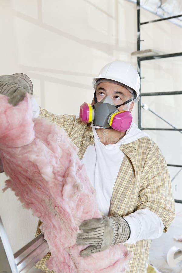 Αρσενικός ανάδοχος που φορά τη μάσκα σκόνης κρατώντας το σφουγγάρι στο εργοτάξιο οικοδομής στοκ εικόνες