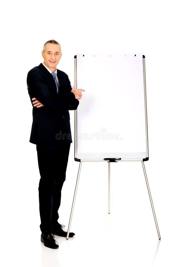 Αρσενικός ανώτερος υπάλληλος που δείχνει στο διάγραμμα κτυπήματος στοκ εικόνα με δικαίωμα ελεύθερης χρήσης