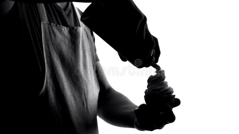 Αρσενικός αρχιμάγειρας που βάζει την κτυπημένη κρέμα στο γλυκό κέικ, ψήνοντας το χόμπι, εύγευστο επιδόρπιο στοκ εικόνες