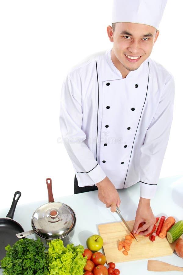 Αρσενικός αρχιμάγειρας που προετοιμάζει κάποια τρόφιμα στοκ εικόνες με δικαίωμα ελεύθερης χρήσης