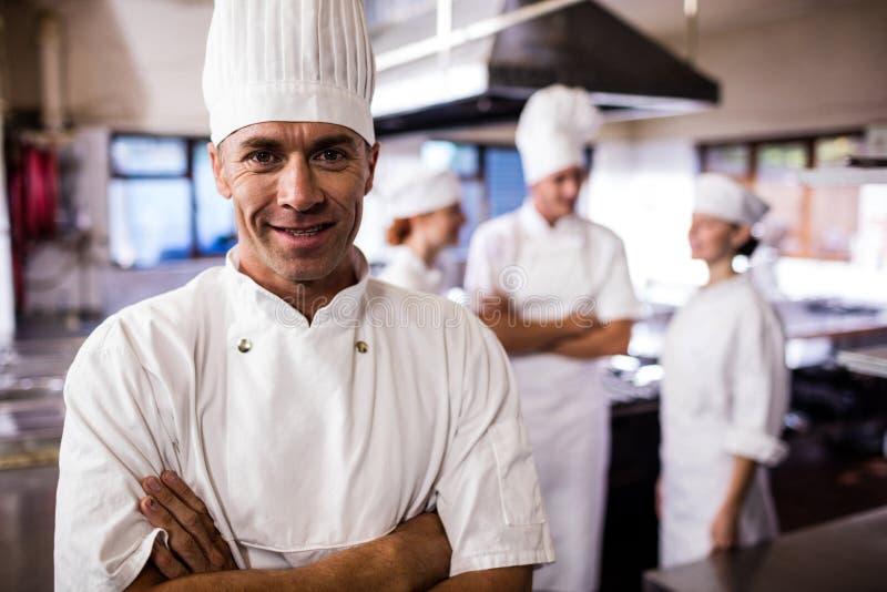 Αρσενικός αρχιμάγειρας που στέκεται με τα όπλα που διασχίζονται ενώ συνάδελφος που αλληλεπιδρά ο ένας με τον άλλον στην κουζίνα στοκ εικόνες