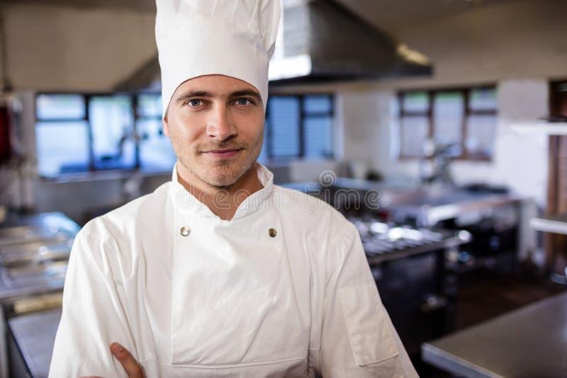 Αρσενικός αρχιμάγειρας που στέκεται στην κουζίνα στο ξενοδοχείο στοκ φωτογραφία