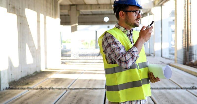 Αρσενικός αρχιτέκτονας με τα σχεδιαγράμματα που χρησιμοποιούν walkie-talkie στοκ εικόνα