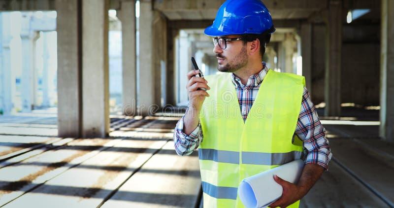 Αρσενικός αρχιτέκτονας με τα σχεδιαγράμματα που χρησιμοποιούν walkie-talkie στοκ εικόνα με δικαίωμα ελεύθερης χρήσης