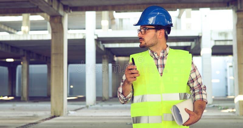 Αρσενικός αρχιτέκτονας με τα σχεδιαγράμματα που χρησιμοποιούν walkie-talkie στοκ εικόνες με δικαίωμα ελεύθερης χρήσης