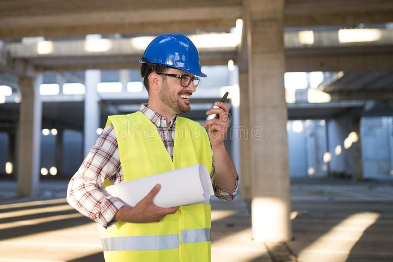 Αρσενικός αρχιτέκτονας με τα σχεδιαγράμματα που χρησιμοποιούν walkie-talkie στοκ φωτογραφίες με δικαίωμα ελεύθερης χρήσης