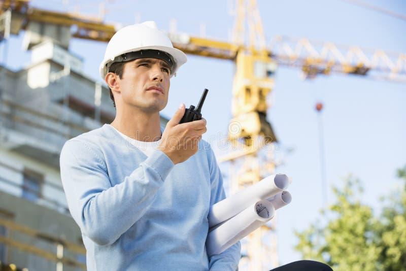 Αρσενικός αρχιτέκτονας με τα σχεδιαγράμματα που χρησιμοποιούν walkie-talkie στο εργοτάξιο οικοδομής στοκ εικόνα