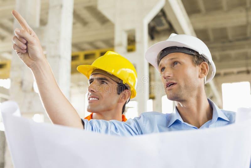 Αρσενικός αρχιτέκτονας που εξηγεί το σχέδιο οικοδόμησης στο συνάδελφο στο εργοτάξιο οικοδομής στοκ εικόνα