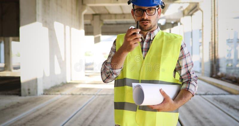 Αρσενικός αρχιτέκτονας που επικοινωνεί walkie-talkie επί του τόπου στοκ φωτογραφία