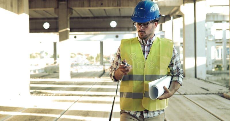 Αρσενικός αρχιτέκτονας που επικοινωνεί walkie-talkie επί του τόπου στοκ εικόνες