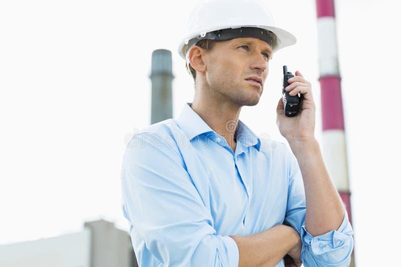 Αρσενικός αρχιτέκτονας που επικοινωνεί walkie-talkie επί του τόπου στοκ φωτογραφία με δικαίωμα ελεύθερης χρήσης
