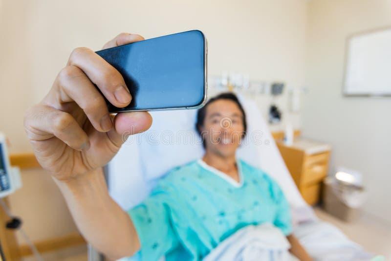 Αρσενικός ασθενής που παίρνει την αυτοπροσωπογραφία μέσω κινητού στοκ εικόνα με δικαίωμα ελεύθερης χρήσης