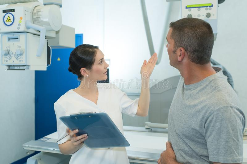 Αρσενικός ασθενής στην των ακτίνων X μηχανή με το θηλυκό γιατρό στοκ εικόνες με δικαίωμα ελεύθερης χρήσης