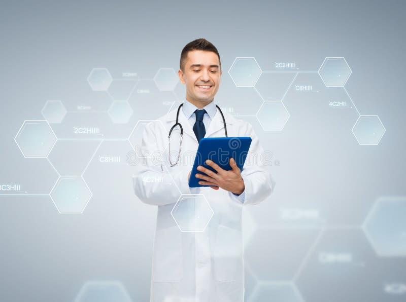 Αρσενικός γιατρός με το PC ταμπλετών και το χημικό τύπο στοκ φωτογραφία