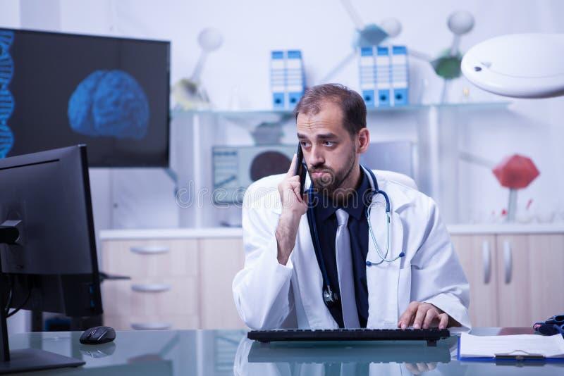 Αρσενικός γιατρός που έχει μια τηλεδιάσκεψη και που μιλά στο τηλέφωνο με έναν ασθενή στοκ φωτογραφίες