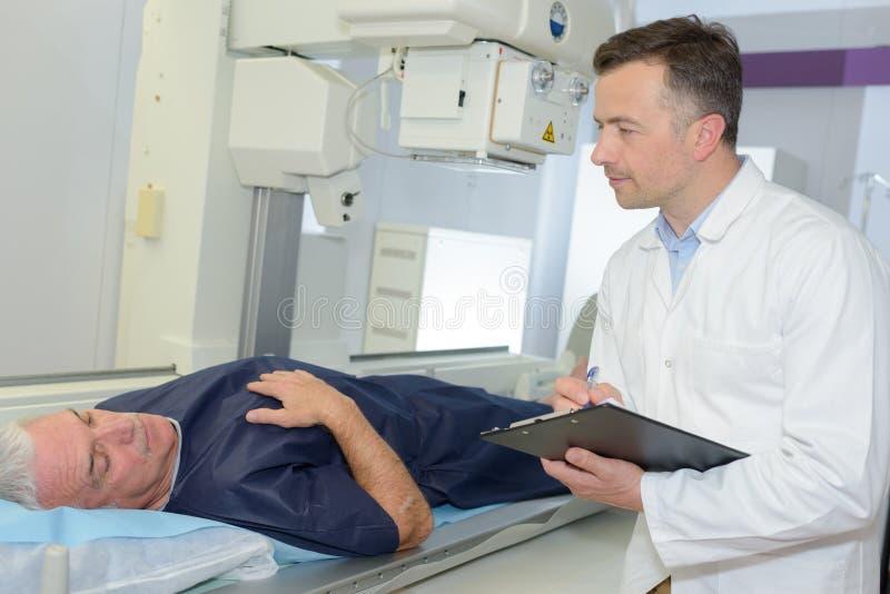 Αρσενικός γιατρός που μιλά στον παλαιό ασθενή και το χαμόγελο στοκ φωτογραφίες