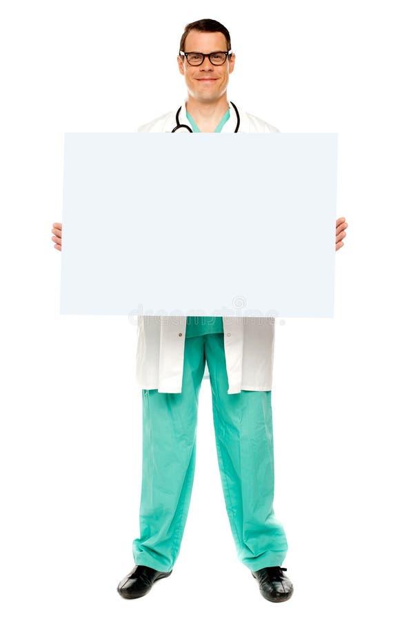 Αρσενικός γιατρός που παρουσιάζει το λευκό διαφημιστικό χαρτόνι στοκ φωτογραφία με δικαίωμα ελεύθερης χρήσης